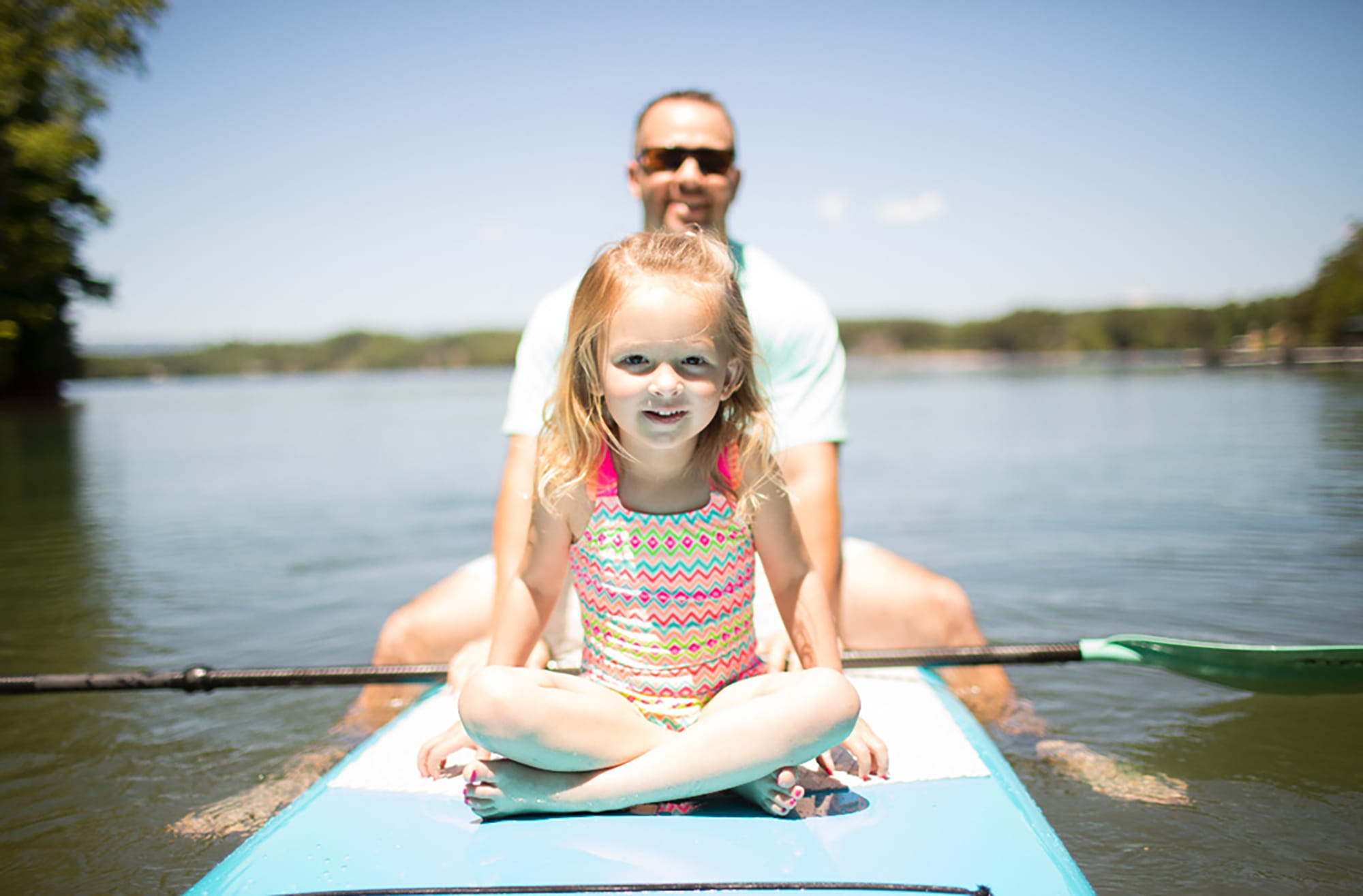 Father and daughter paddleboarding on the lake